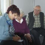 Seniorenassistentin schreibt Einkaufszettel
