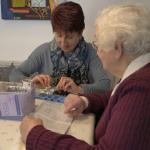 Senioren und Assistentin richten Tabletten her